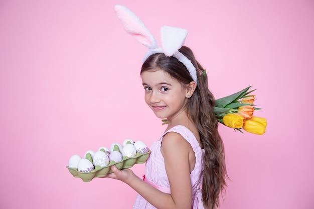 Kleines mädchen mit osterhasenohren hält einen strauß tulpen und ein tablett eier in ihren händen auf einer rosa wand.