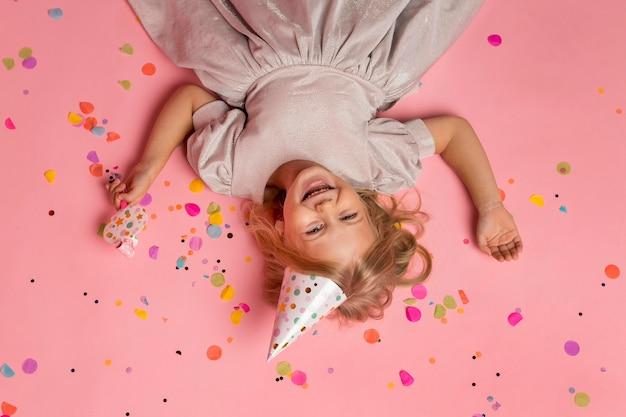 Kleines mädchen mit partyhut und konfetti