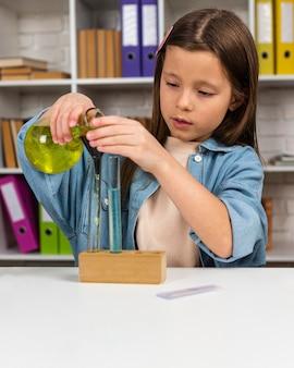Kleines mädchen mit reagenzgläsern und mikroskop