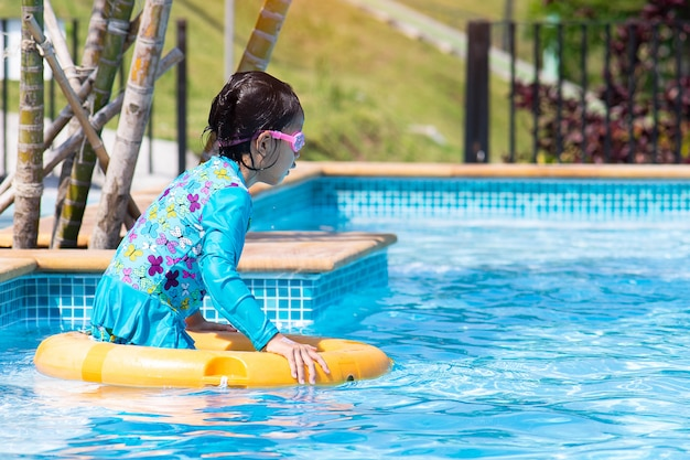 Kleines mädchen mit rettungsring im pool schwimmen.