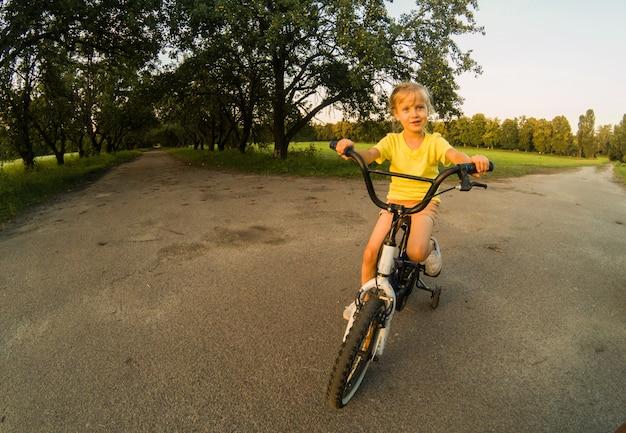 Kleines mädchen mit ridg fahrrad am sonnenuntergang