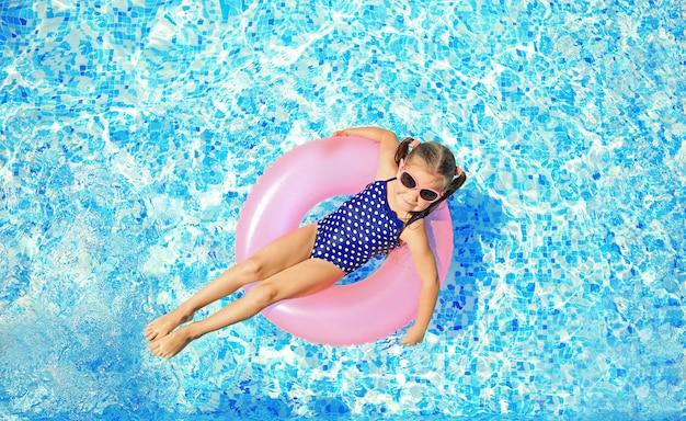 Kleines mädchen mit rosa gummiring im schwimmbad