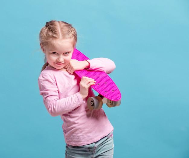 Kleines mädchen mit rosa skateboard