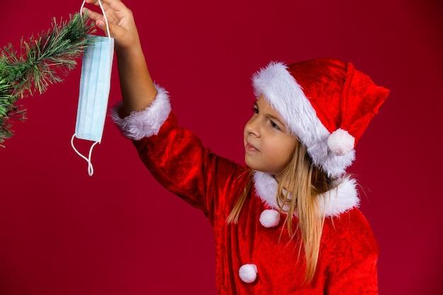 Kleines mädchen mit rotem hut und santa kleidung schmückt den weihnachtsbaum mit einer chirurgischen maske