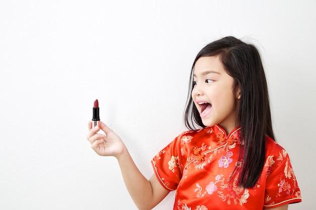Kleines mädchen mit rotem lippenstift