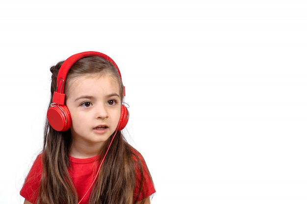 Kleines mädchen mit roten kopfhörern.
