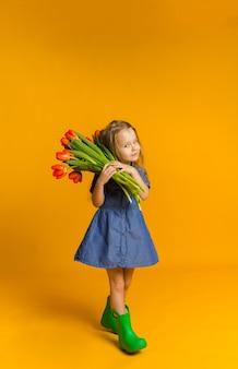 Kleines mädchen mit roten tulpen auf einer gelben wand