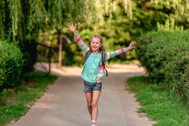Kleines mädchen mit rucksack, der nach der schule entlang der parkstraße nach hause geht