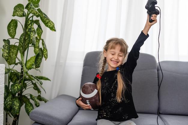 Kleines mädchen mit rugbyball und joystick zum spielen von videospielen zu hause