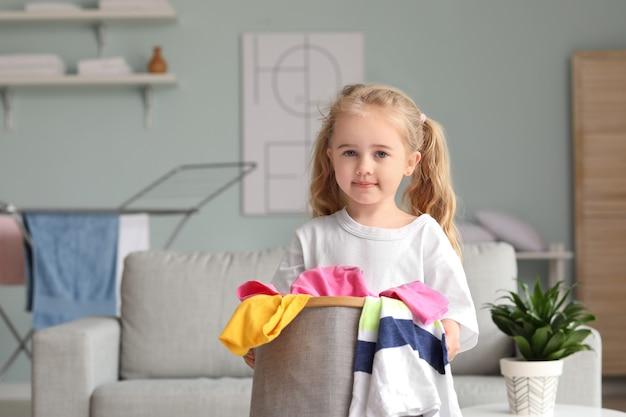 Kleines mädchen mit schmutziger wäsche zu hause