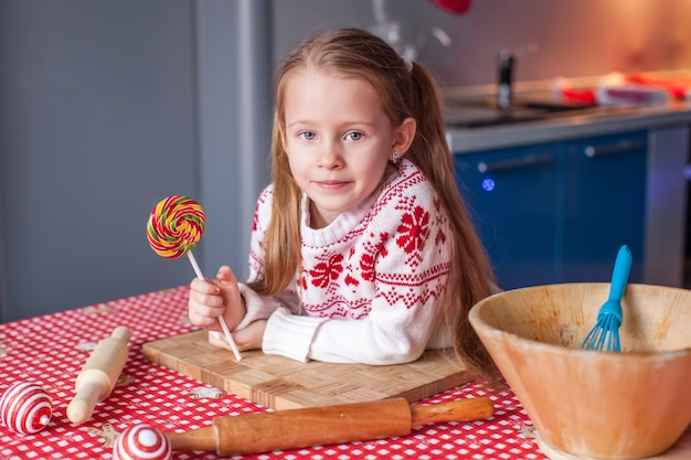 Kleines mädchen mit süßigkeit in der hand bereitet weihnachtskuchen zu
