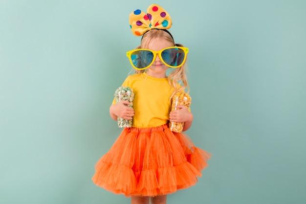 Kleines mädchen mit süßigkeiten und großer sonnenbrille