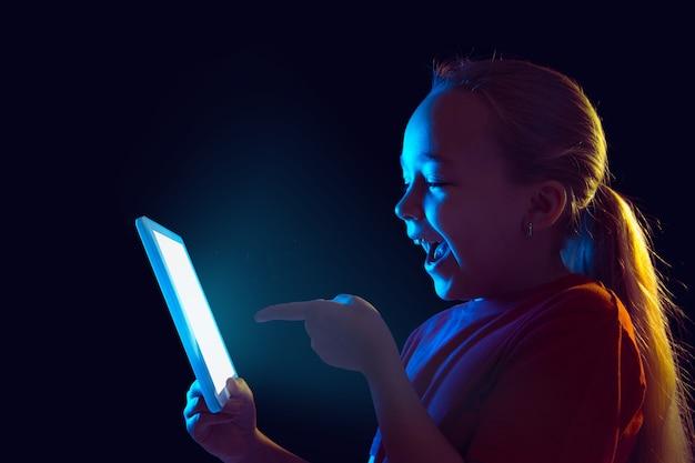 Kleines mädchen mit tablette im neonlicht