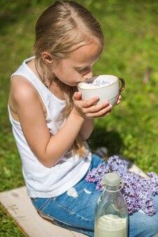 Kleines mädchen mit tasse milch auf natur