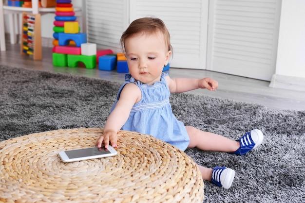 Kleines mädchen mit telefon auf teppich