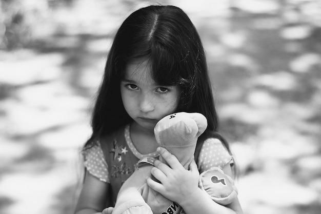 Kleines mädchen mit traurigem gesicht einen teddy halten