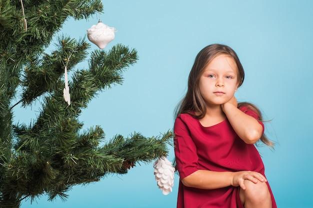 Kleines mädchen mit weihnachtsbaum auf blauem hintergrund