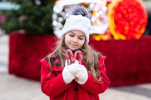 Kleines mädchen mit weihnachtsbonbons auf der straße