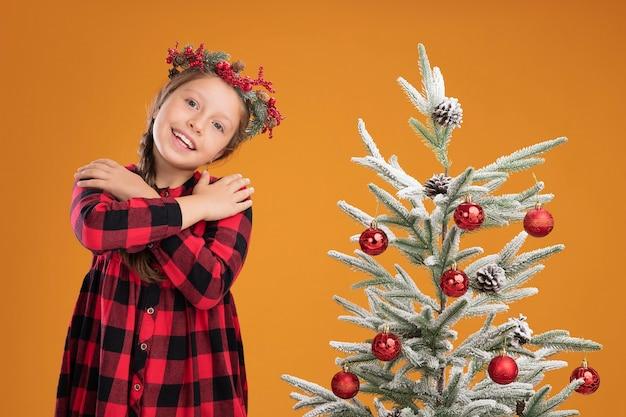 Kleines mädchen mit weihnachtskranz in kariertem hemd, das die hände auf der brust hält, glücklich und positives gefühl, dankbar neben einem weihnachtsbaum über orangefarbener wand zu stehen
