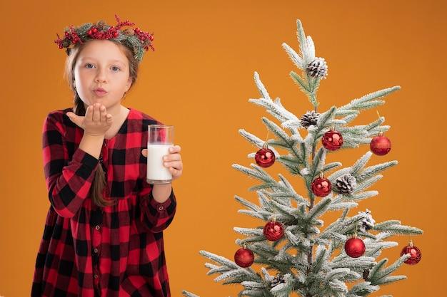 Kleines mädchen mit weihnachtskranz in kariertem hemd, das ein glas milch hält, glücklich und positiv einen kuss bläst, der neben einem weihnachtsbaum über einer orangefarbenen wand steht