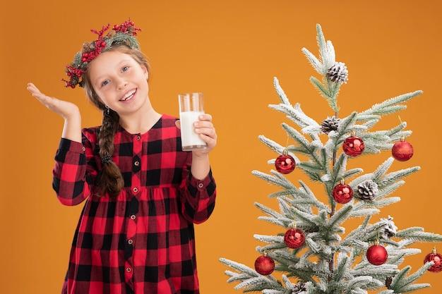 Kleines mädchen mit weihnachtskranz in kariertem hemd, das ein glas milch hält, glücklich und positiv lächelnd, fröhlich neben einem weihnachtsbaum über orangefarbener wand stehen standing