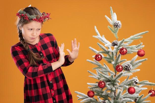 Kleines mädchen mit weihnachtskranz in kariertem hemd, das neben einem weihnachtsbaum steht und ihn mit angewidertem gesichtsausdruck betrachtet, der die hände ausstreckt und eine verteidigungsgeste über der orangefarbenen wand macht