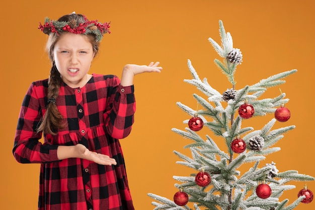 Kleines mädchen mit weihnachtskranz in kariertem hemd, das neben einem weihnachtsbaum steht und verwirrt aussieht, als er die arme vor unmut und empörung über die orangefarbene wand hebt