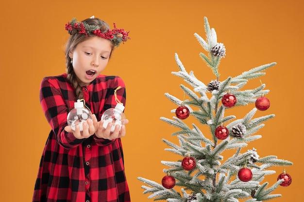 Kleines mädchen mit weihnachtskranz in kariertem hemd, das weihnachtskugeln hält und sie verwirrt und überrascht ansieht, neben einem weihnachtsbaum über einer orangefarbenen wand zu stehen