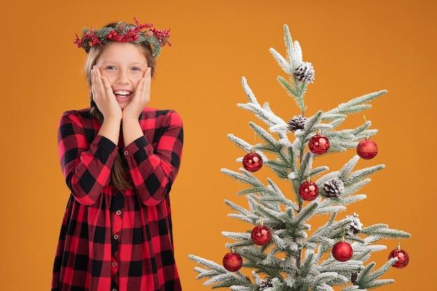 Kleines mädchen mit weihnachtskranz in kariertem hemd erstaunt und überrascht, neben einem weihnachtsbaum über orangefarbener wand zu stehen