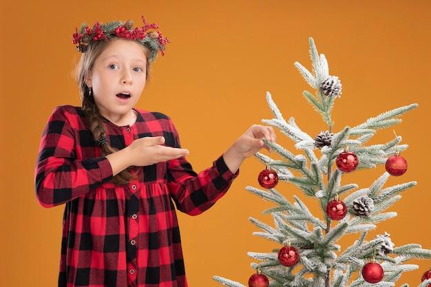 Kleines mädchen mit weihnachtskranz in kariertem kleid, das den weihnachtsbaum schmückt, der verwirrt und überrascht aussieht, der mit dem handarm über der orangefarbenen wand steht
