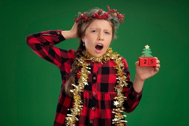 Kleines mädchen mit weihnachtskranz in kariertem kleid mit lametta um den hals, das spielzeugwürfel mit weihnachtsdatum hält, die mit der hand auf dem kopf über grüner wand verwechselt wird