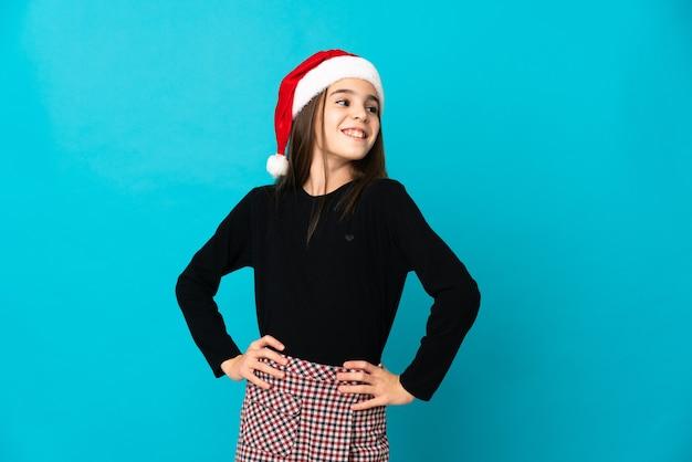 Kleines mädchen mit weihnachtsmütze auf blauem hintergrund isoliert posiert mit armen an der hüfte und lächelnd