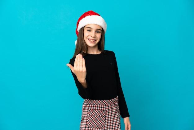 Kleines mädchen mit weihnachtsmütze lokalisiert auf blauem hintergrund, der einlädt, mit hand zu kommen. schön, dass du gekommen bist