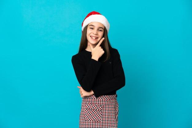 Kleines mädchen mit weihnachtsmütze lokalisiert auf blauem hintergrund glücklich und lächelnd