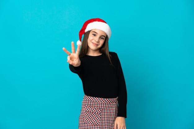 Kleines mädchen mit weihnachtsmütze lokalisiert auf blauem hintergrund glücklich und zählt drei mit den fingern