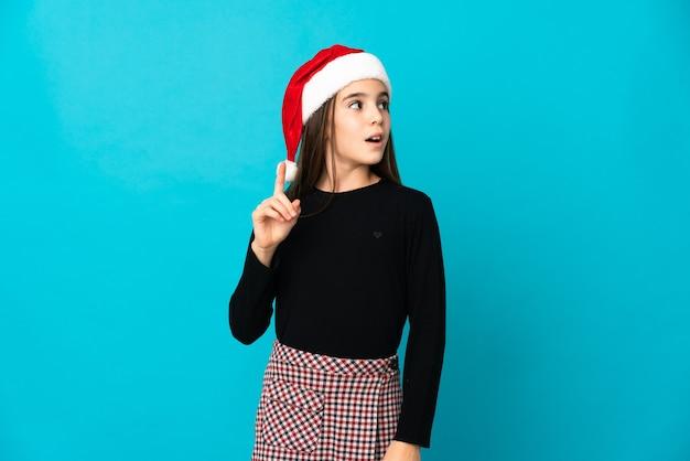 Kleines mädchen mit weihnachtsmütze lokalisiert auf blauer wand, die eine idee denkt, die den finger nach oben zeigt
