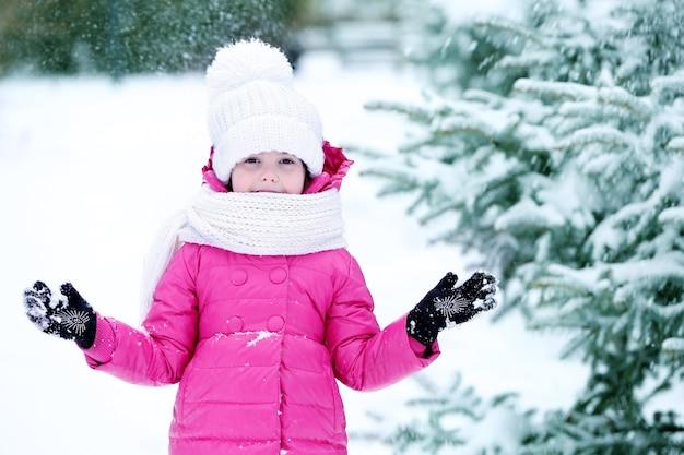 Kleines mädchen mit winterkleidung, das spaß im verschneiten park im freien hat