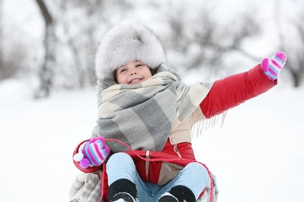 Kleines mädchen mit winterkleidung, die spaß auf schlitten im verschneiten park im freien hat