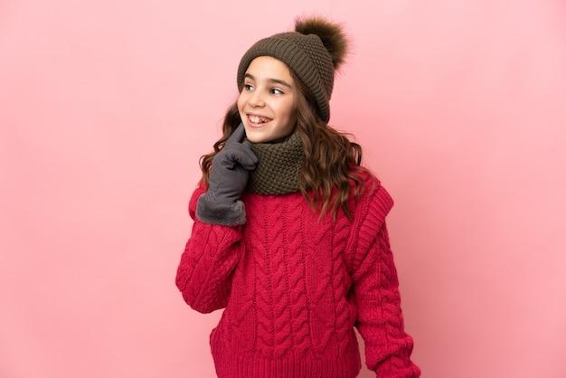 Kleines mädchen mit wintermütze lokalisiert auf rosa wand, die eine idee beim nachschlagen denkt
