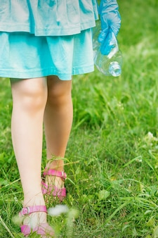Kleines mädchen mit zerknitterter plastikflasche in ihrer hand beim reinigen des mülls im park
