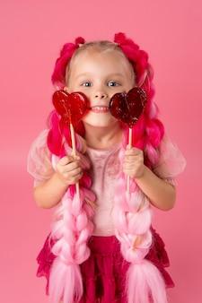 Kleines mädchen mit zöpfen aus rosa kanekalon hält einen herzförmigen lutscher auf einem rosa hintergrund