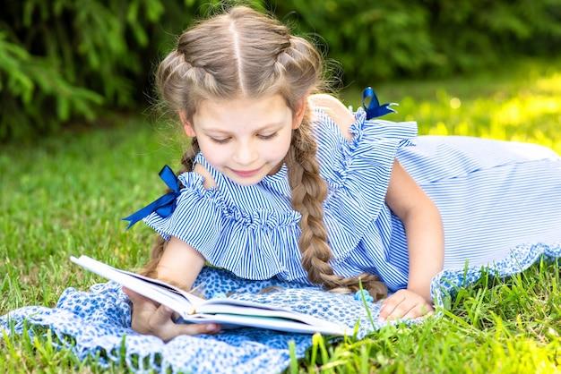 Kleines mädchen mit zöpfen liest ein buch, das auf dem grünen gras im park liegt.
