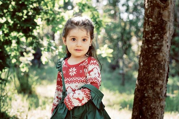 Kleines mädchen mitten im wald und lächelt. sie trägt ein grünes kleid und eine rote bluse