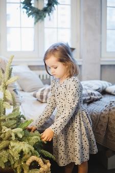 Kleines mädchen nahe einem kleinen weihnachtsbaum, inneneinrichtung für das neue jahr und weihnachten, bett, fenster