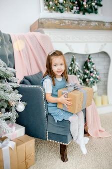 Kleines mädchen nahe einem weihnachtsbaum mit spielwaren, nahe bei einem kamin