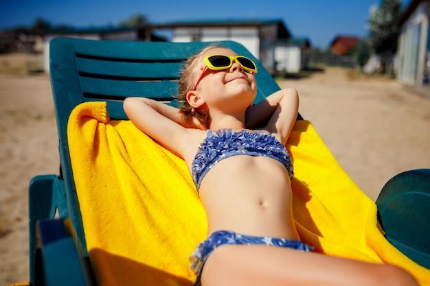 Kleines mädchen nimmt auf einem sunbed nahe dem pool am erholungsort ein sonnenbad