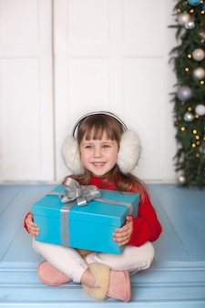 Kleines mädchen öffnet weihnachtsgeschenk auf veranda des hauses.