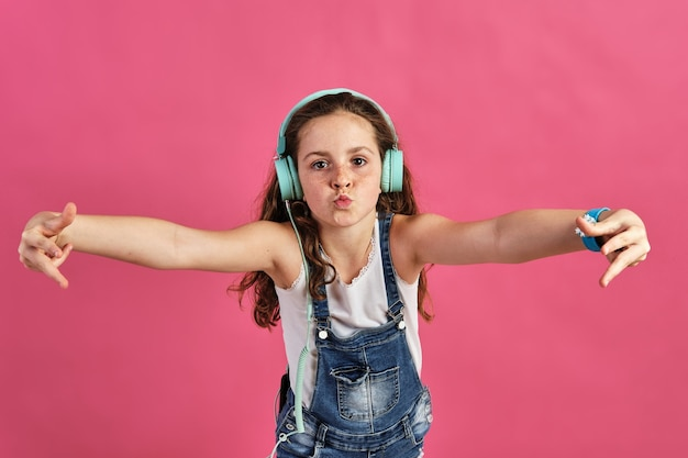 Kleines mädchen posiert mit kopfhörern beim hören lauter musik auf einem rosa