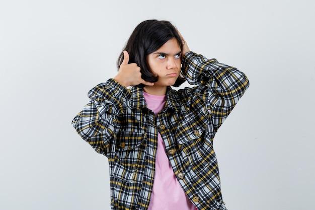 Kleines mädchen posiert wie telefonieren im hemd, vorderansicht der jacke.