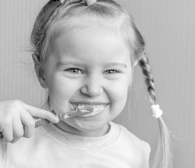 Kleines mädchen putzt sich die zähne und lächelt
